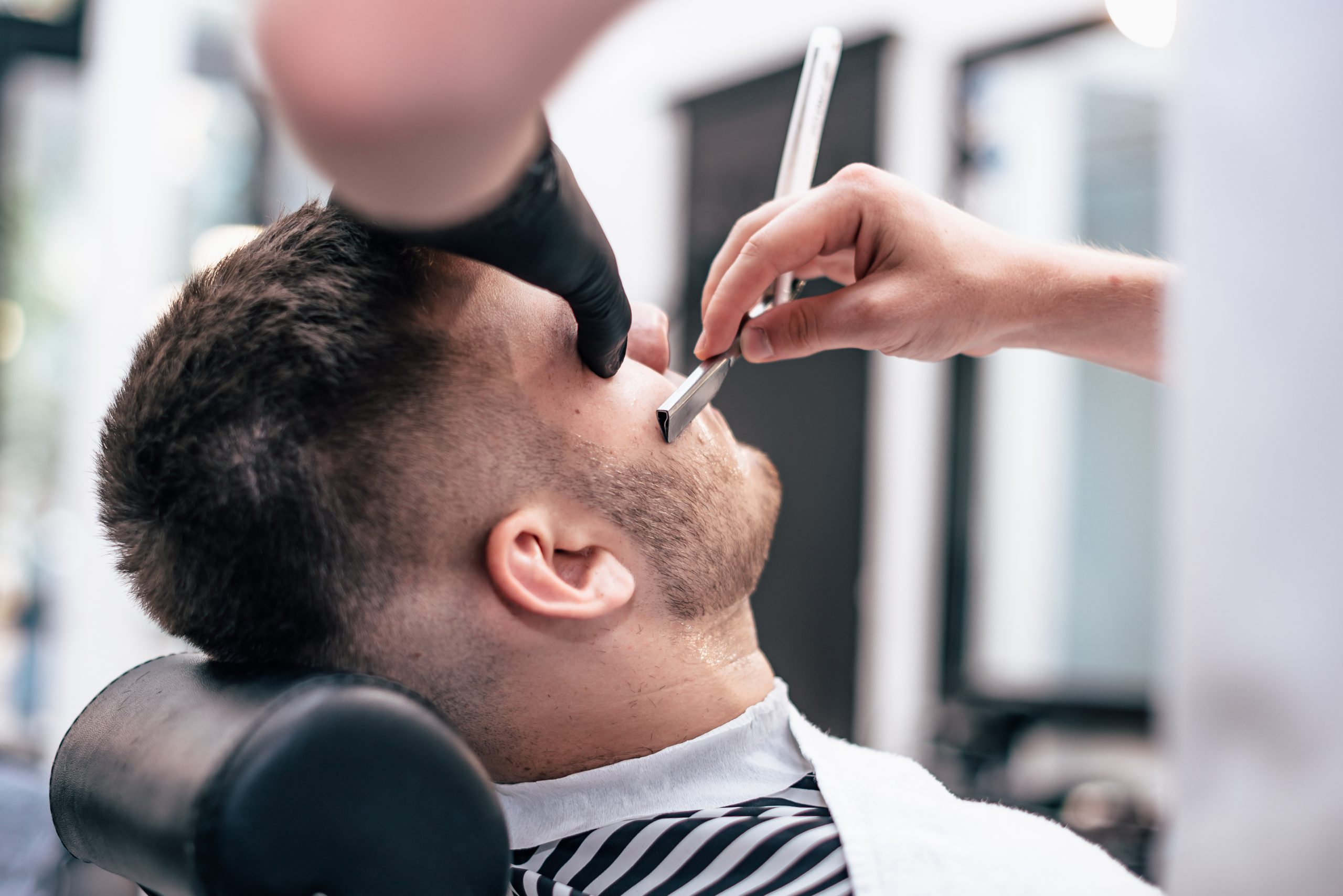 Barber makes a haircut to the client.